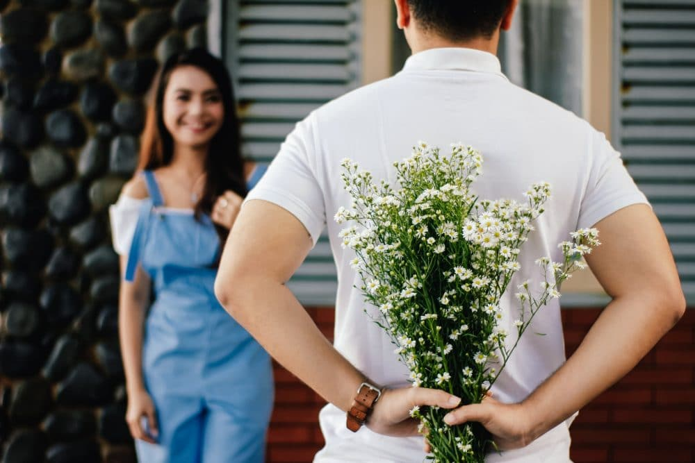 man giving woman flowers dating app online